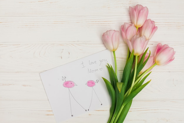 Flowers bunch and child drawing on wooden desk Free Photo