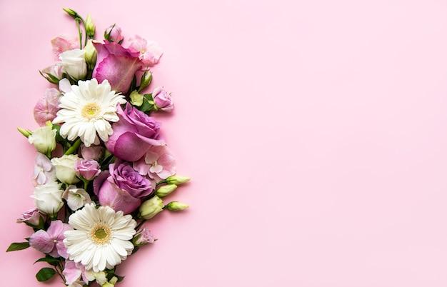 花の組成物。ピンクのピンクの花で作られたボーダー。 Premium写真