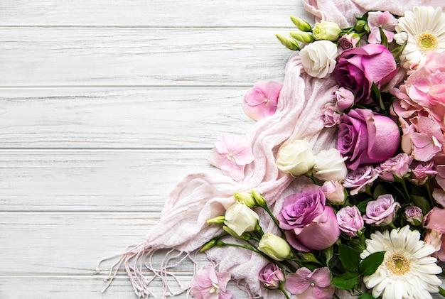 花の組成物。白い木製のピンクの花で作られたボーダー。 Premium写真