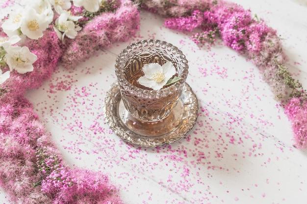 花の組成白地に紅茶のグラスとピンクの花で作られたサークル Premium写真