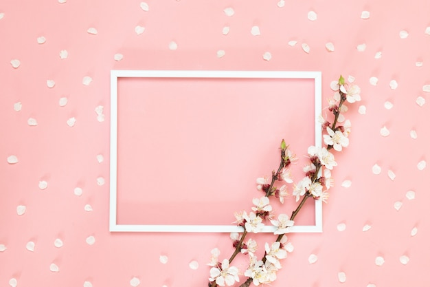 Flowers composition creative. blank photo frame, pink flowers on living coral background, copy space. Premium Photo