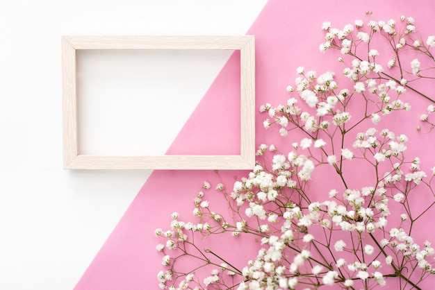 Flowers composition romantic. white gypsophila flowers, photo frame on pastel pink background. Premium Photo