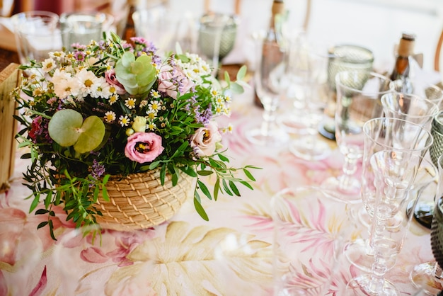 Flowers decorating the centerpieces with luxury cutlery on the tables of a wedding hall. Premium Photo