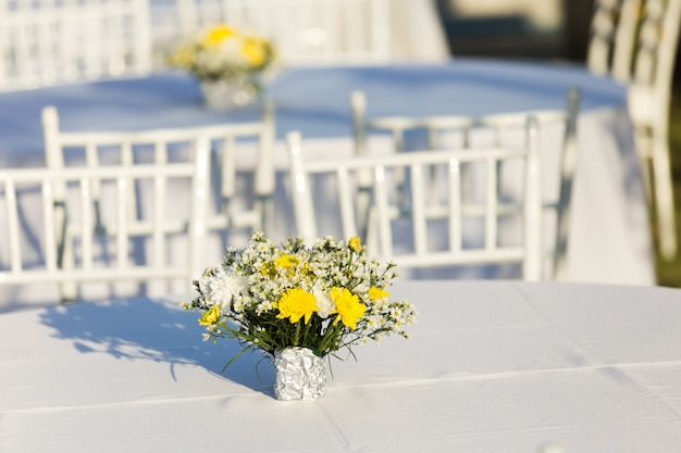 Flowers decoration on white table outdoor in  wedding reception Premium Photo
