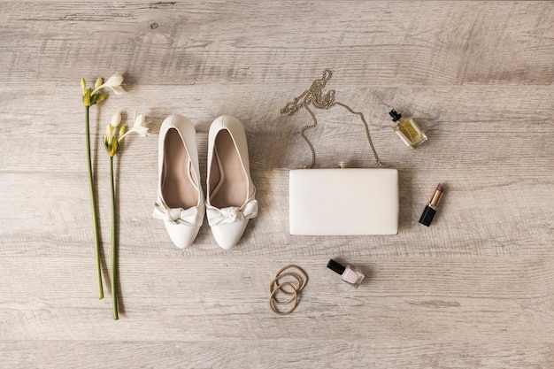 Flowers; dress shoes; clutch; perfume; lipstick; nail varnish and hairbands on wooden backdrop Free Photo