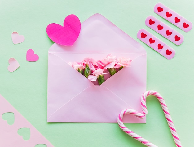 Flowers in envelope with paper hearts Free Photo