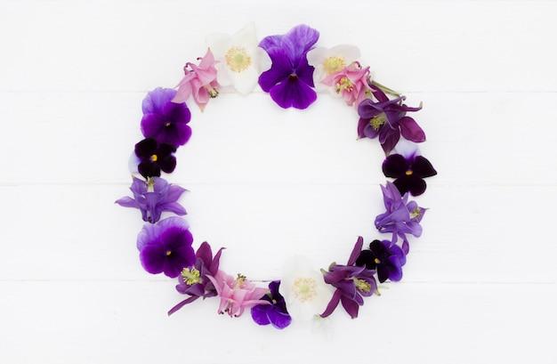 Плоский дизайн цветы. цветочная круглая рамка, венок из цветов с фиолетовыми, пурпурными, розовыми белыми цветами. шаблон с копией пространства на белой деревянной доске Premium Фотографии