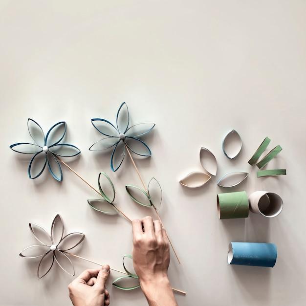 母の日のトイレットペーパーチューブの花、子供向けのゼロウェイストクラフト、ニュートラルなパステルカラーの表面 Premium写真
