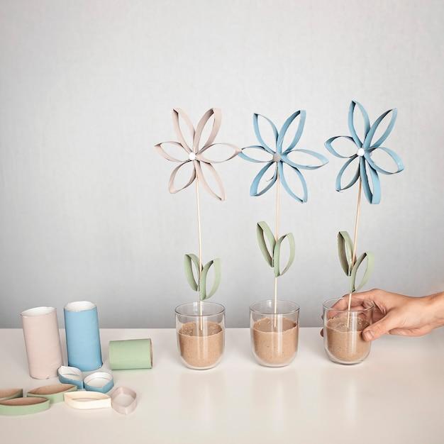 母の日のトイレットペーパーチューブの花、子供のためのゼロウェイストクラフト、ニュートラルなパステルカラーの壁 Premium写真