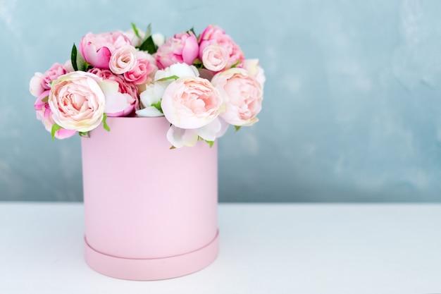 둥근 고급 선물 상자에 꽃입니다. 종이 상자에 분홍색과 흰색 모란의 꽃다발. 텍스트 무료 Copyspace와 꽃의 모자 상자의 모형. 파스텔 색상의 인테리어 장식. 프리미엄 사진