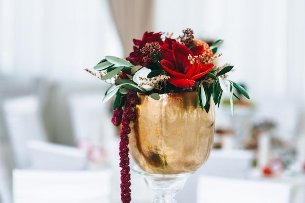 結婚式のテーブルに金色の小さなヴィンテージの花瓶の花。結婚式前のレストラン。 Premium写真