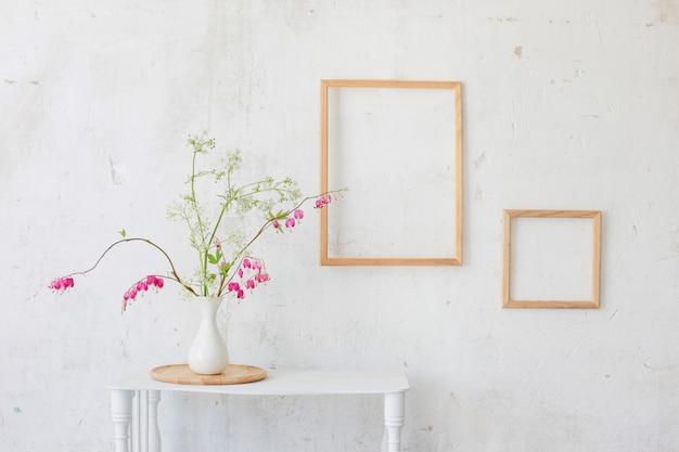 Цветы в вазе на фоне белой стены Premium Фотографии