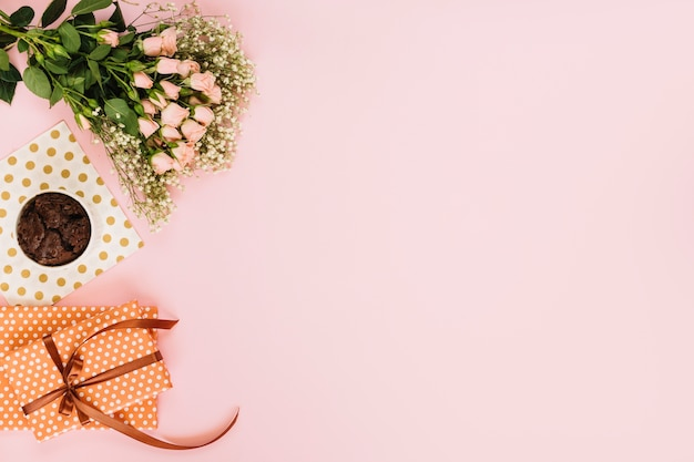 Flowers near dessert and gifts Free Photo