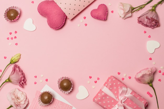 Flowers near hearts, present box and chocolate candies Free Photo