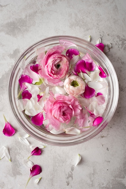 Flowers petals in bowl on table Free Photo