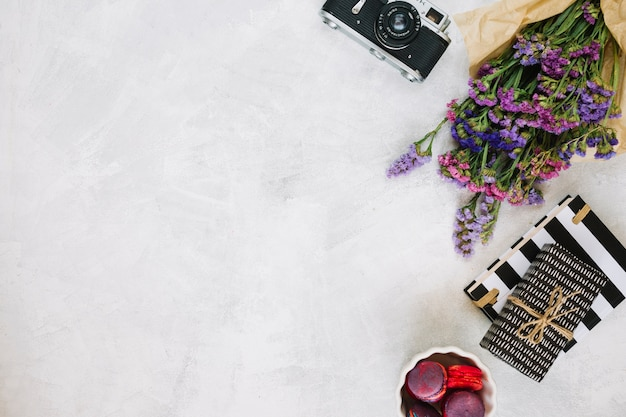 Flowers and retro camera near gifts and macaroons Free Photo