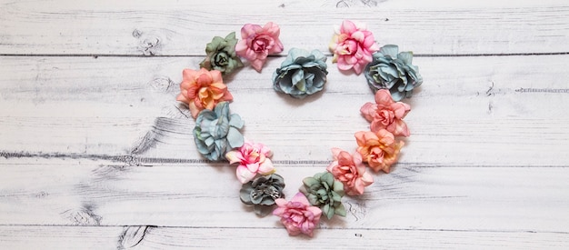 Flowers in the shape of a heart on a wooden background. Premium Photo