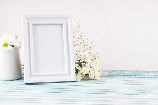 Flowers with blank frame on table Free Photo