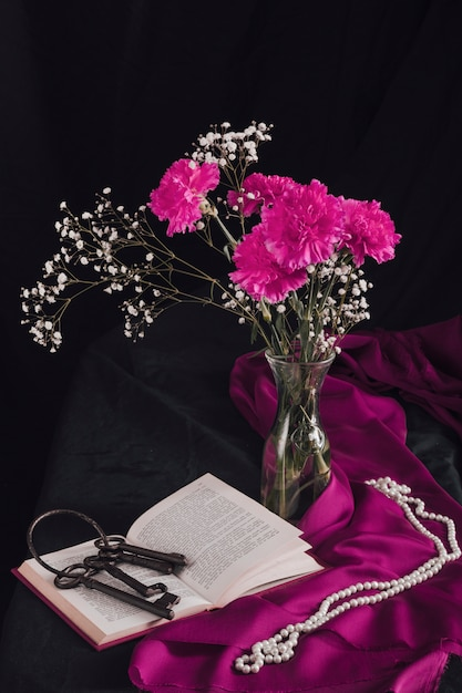 Flowers with bloom twigs in vase near keys on volume and beads on purple textile in darkness Free Photo