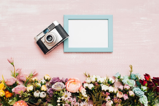 Flowers with blue frame and vintage camera Free Photo