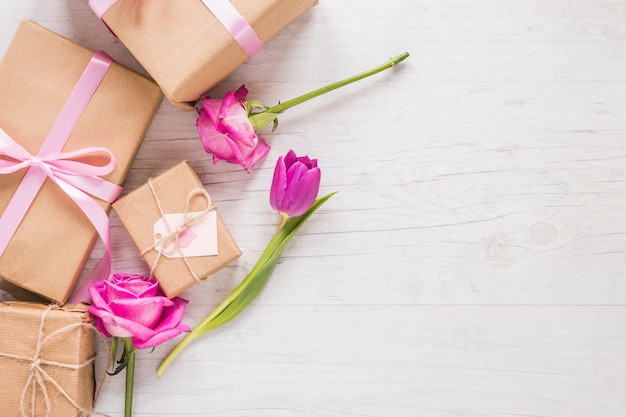 Flowers with gift boxes on table Free Photo