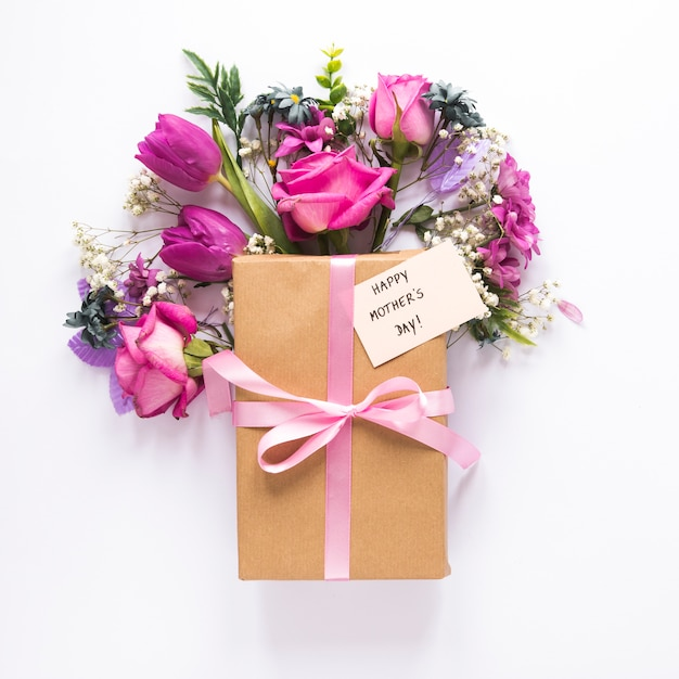 Flowers with gift and happy mothers day inscription Free Photo