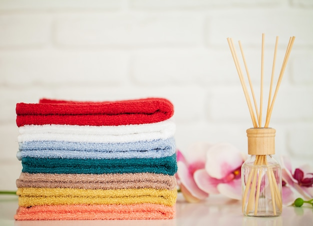 Fluffy bath towels on light wooden table with aroma sticks Premium Photo