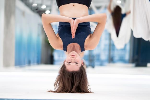 Женщина висит вниз головой в гамаке. fly йога класс. Бесплатные Фотографии