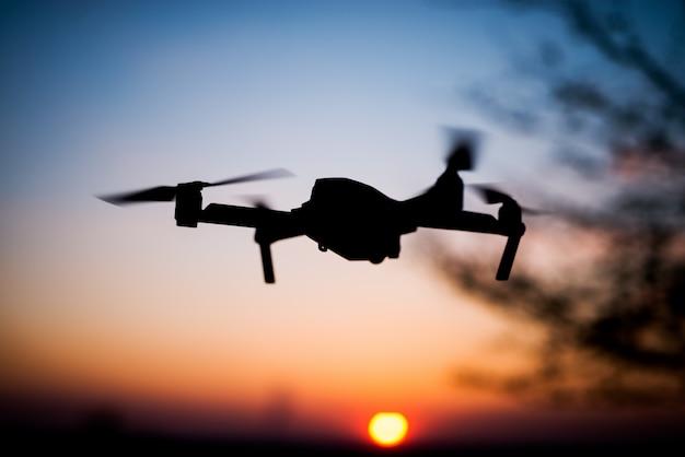 ドローンを夕日に飛ばします。太陽に対するシルエット。動きのクワッドヘリコプター。 Premium写真