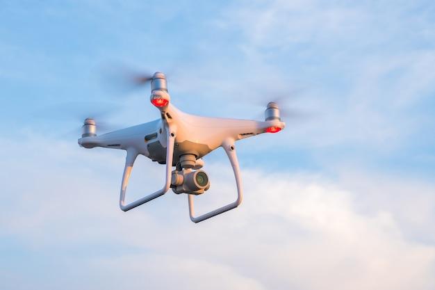青い空と飛行ドローン。 Premium写真