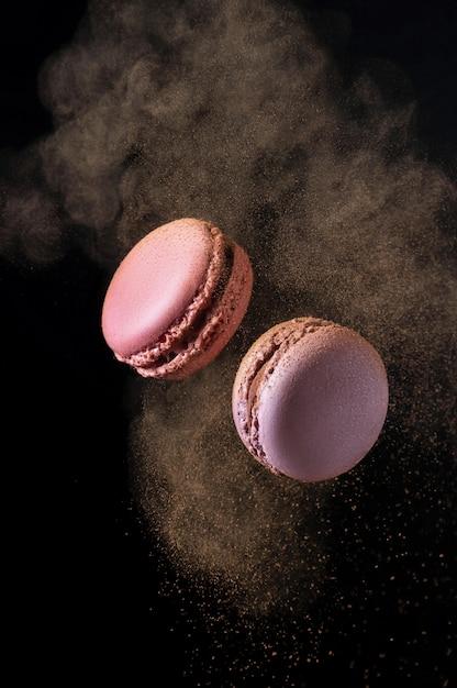 Летающие французские розовые и фиолетовые миндальные печенья с какао-порошком Premium Фотографии
