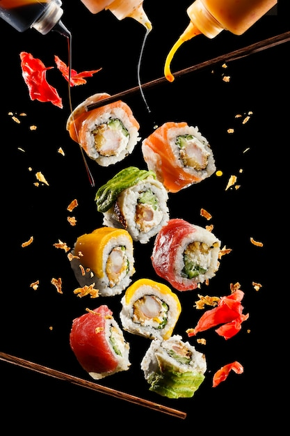 Flying pieces of sushi with wooden chopsticks and sauce Premium Photo
