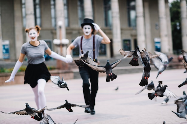 Flying pigeons near running mime couple Free Photo