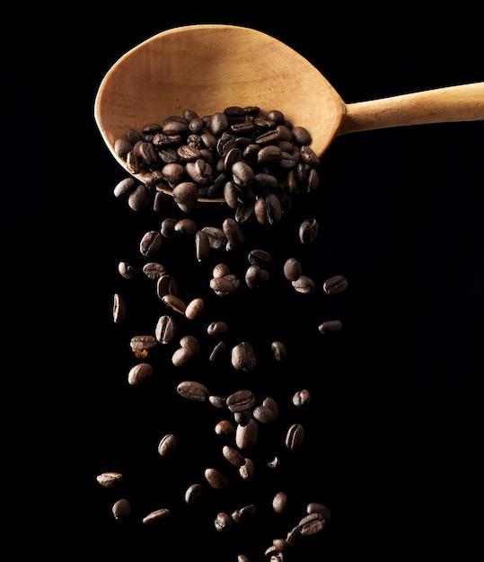 黒い空間にローストコーヒーの穀物を飛んでください。 Premium写真