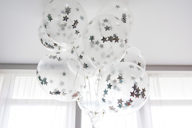 Flying white balloons with silver stars under the ceiling Premium Photo