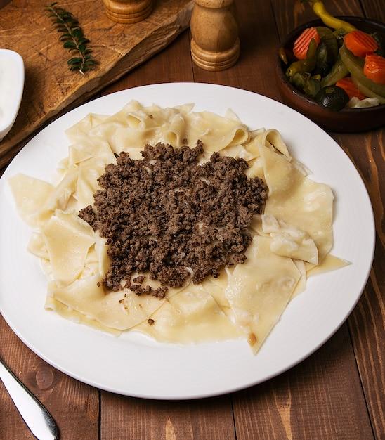 白人の伝統的なfoのkhingal、ヒンカリ語。木製のテーブルの上の白い皿に肉と白人のパスタ。 無料写真