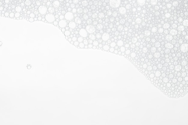 Foam bubbles from soap or shampoo washing on white background. Premium Photo