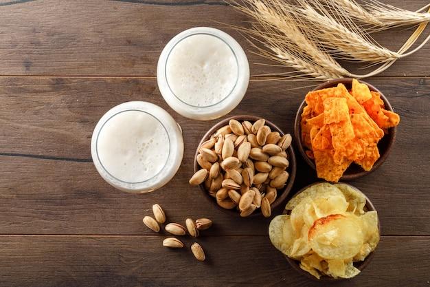 Пенное пиво в бокалах с фисташками, колосья пшеницы, вид сверху чипсы на деревянном столе Бесплатные Фотографии