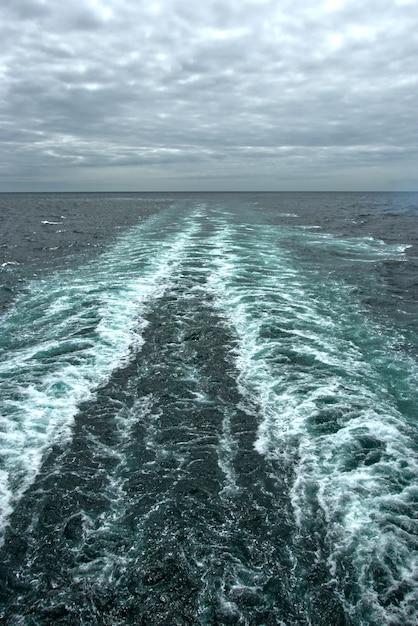 Onde schiumose sulla superficie dell'acqua dietro la nave da crociera Foto Gratuite