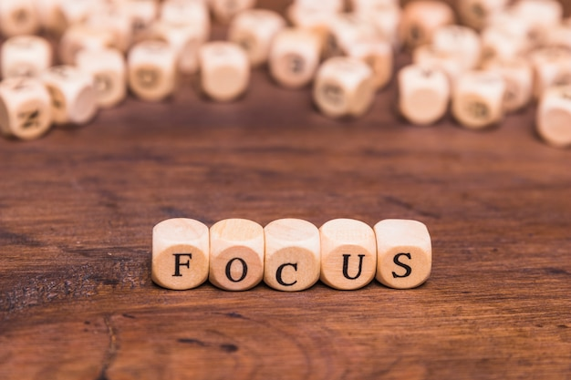 Focus letters written on wooden cubes over table Free Photo