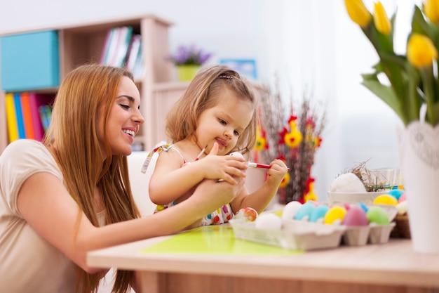 母親と一緒にイースターエッグを描く少女に焦点を当てる 無料写真