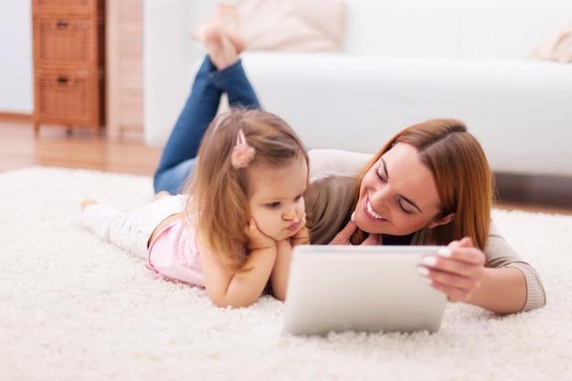 집에서 디지털 태블릿을 사용하는 엄마와 어린 소녀 집중 무료 사진
