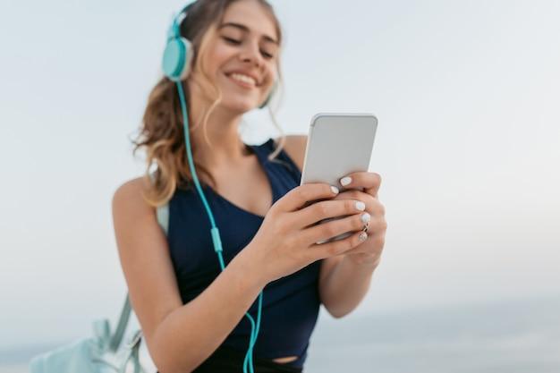 海でヘッドフォンを通して音楽を聴いて、電話でチャットスポーツウェアで幸せな若い女性の手に焦点を当てます。笑顔で真のポジティブな感情を表現 無料写真