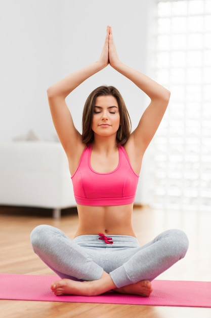 Focus woman doing yoga at home Free Photo