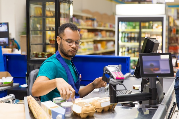 Focused african american cashier scanning goods at checkout Free Photo