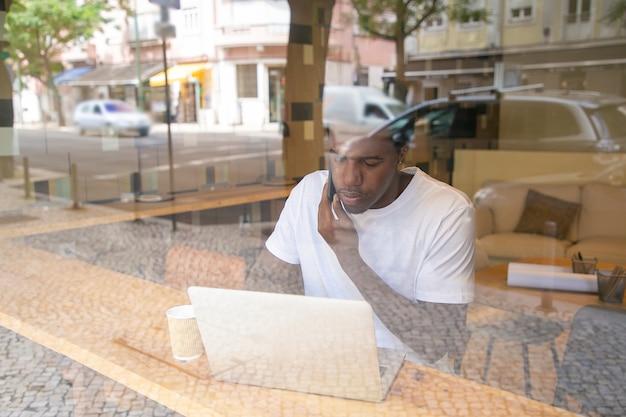 ラップトップで働いて、コワーキングスペースで携帯電話で話すアフリカ系アメリカ人の起業家に焦点を当てた 無料写真