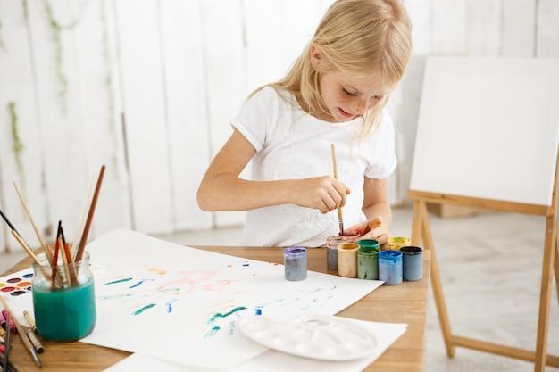 焦点を合わせてインスピレーションを得た小さなブロンドの女の子がブラシをペイントに深く混ぜ、それを混ぜます。絵画で占められた白いtシャツの女性のそばかすのある子供。 無料写真