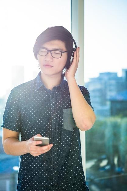 Focused asian businessman listening to music in office Premium Photo