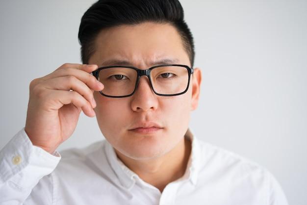 b0db3cf6f39 Focused asian man trying to see through glasses Premium Photo