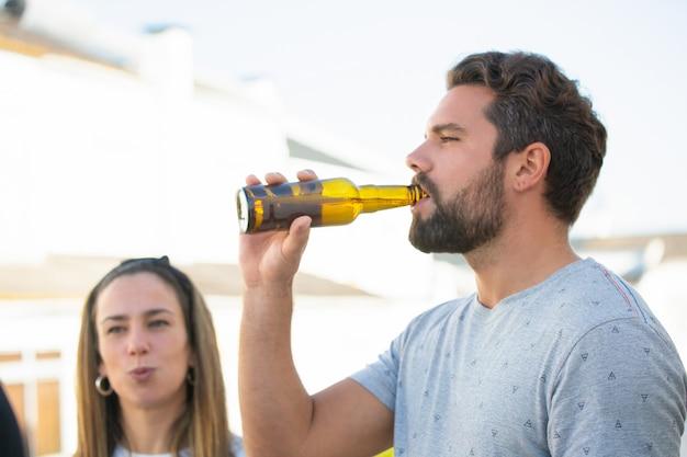 Focused bearded guy enjoying beer with friends Free Photo